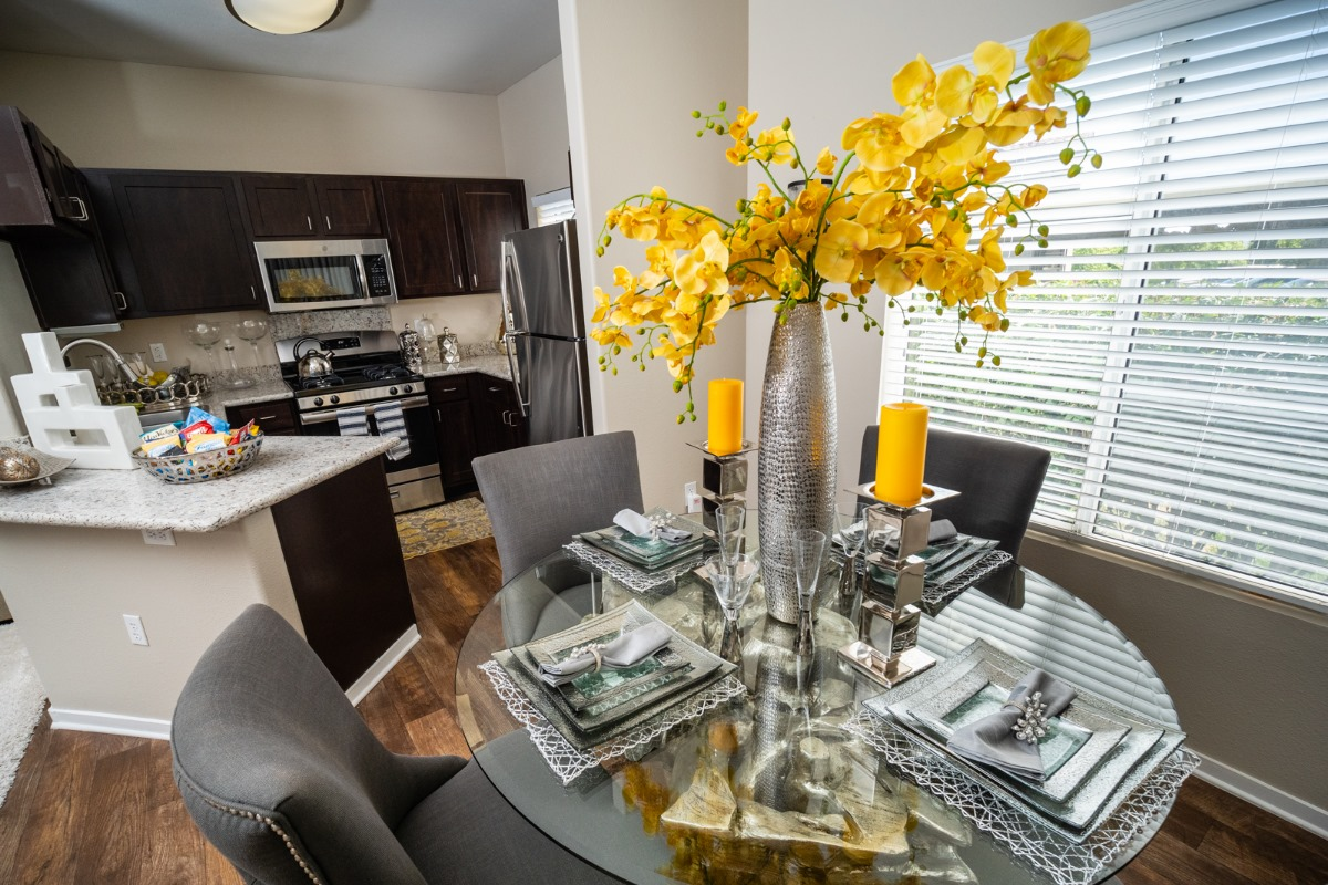 short term housing with glass dining table with yellow flower arrangement, candles, and silverware. There is granite kitchen in the background.
